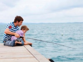 image of man and boy fishing from dock