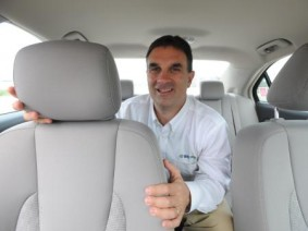 Jeff Schultheis of Bio100 inside a car holding a seat rest.