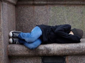 young teen sleeping on concrete bench