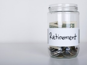 """dollars and coins in jar labeled """"Retirement"""""""