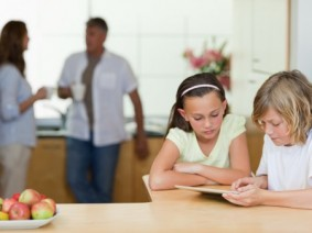 image of kids using mobile device with parents in the background