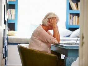 older adult in front of laptop feeling anxious