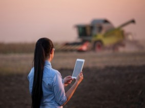 A woman uses her tablet to calculate harvest in a farm field. Women are now managing or partly managing 40 percent of Ohio's farms.