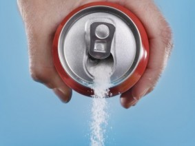 can of soda with sugar pouring out of the opening
