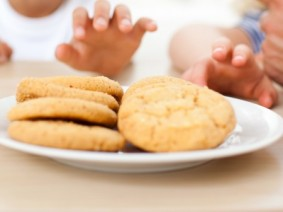 children's hands moving toward a plate of cookies
