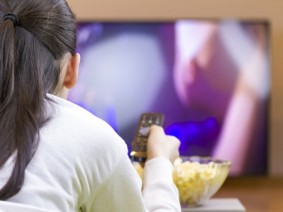 girl watching tv with remote and a bowl of popcorn