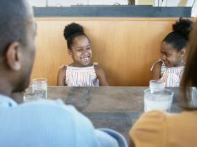 children in restaurant with parents across from them