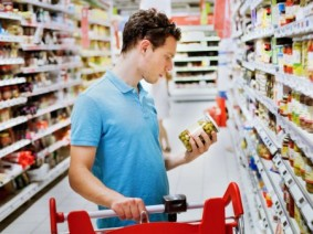 man examining food label in grocery store aisle
