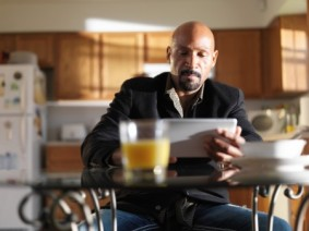 man with laptop at kitchen breakfast table