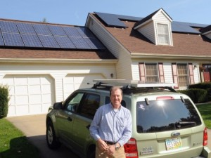 Fred Michel at his solar-powered house, next to his solar-charged hybrid vehicle. (Photo by Ken Chamberlain)
