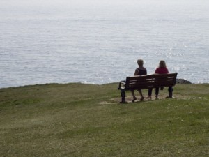 mother and daughter sitting apart on a bench facing a body of water