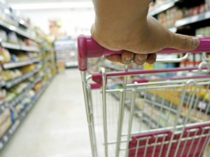 stock image of shopper with cart in grocery aisle