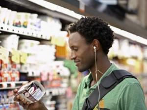man looking at yogurt in grocery store