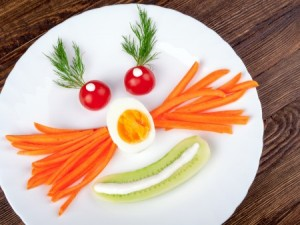 veggies on a plate in the form of a funny face
