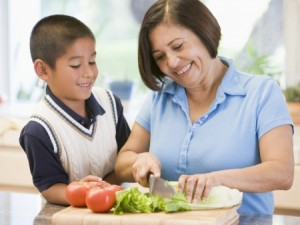 grandson with grandmother making a salad