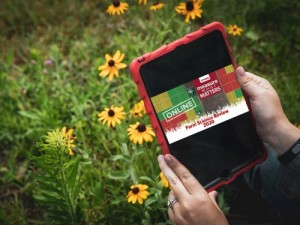 A tablet showing FSR content held by someone in a flower patch.