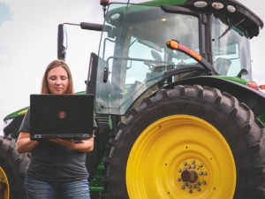 Female farmer holding a laptop while standing in front of a tractor